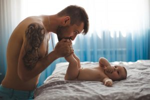 Tattooed dad kissing small baby's feet.